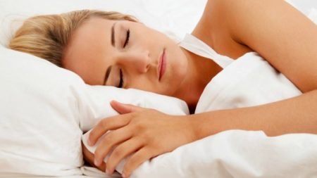 a pretty young woman sleeping in bed recovering.